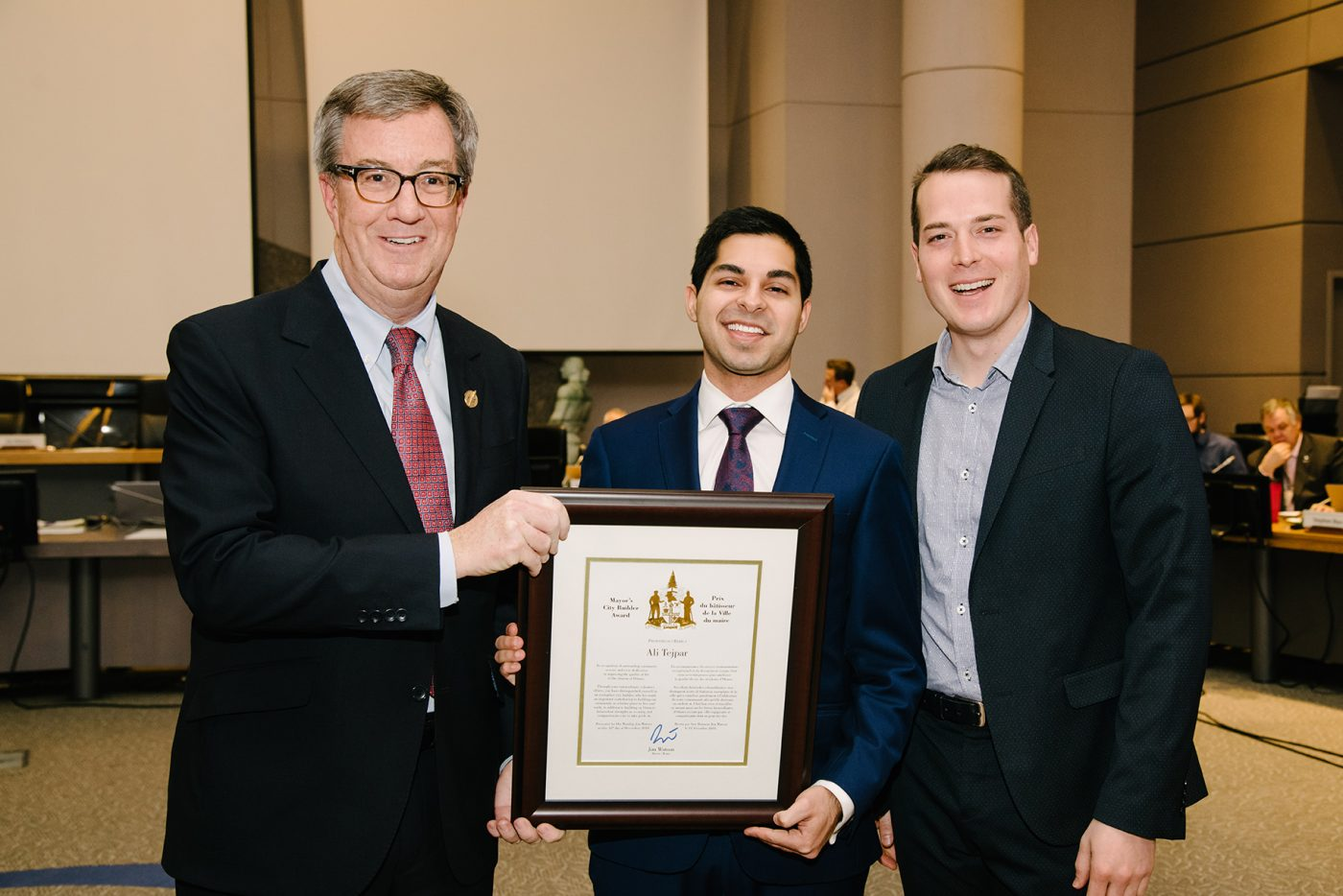 Ali Tejpar holds a certificate with Jim Watson and Mathieu Fleury on either side of him.