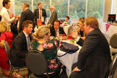 Guests chatting at dinner tables.