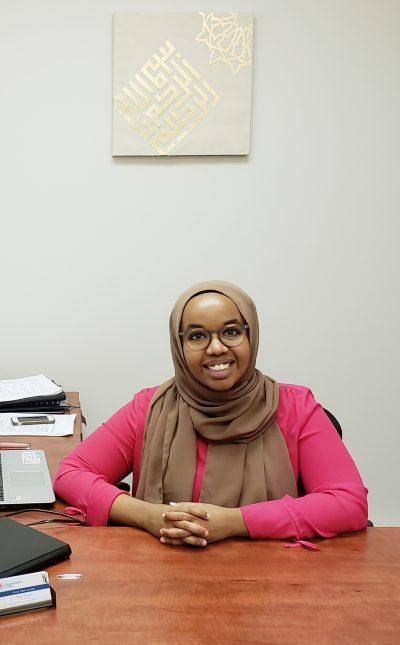 Adar Abdulkadir sitting at her desk.