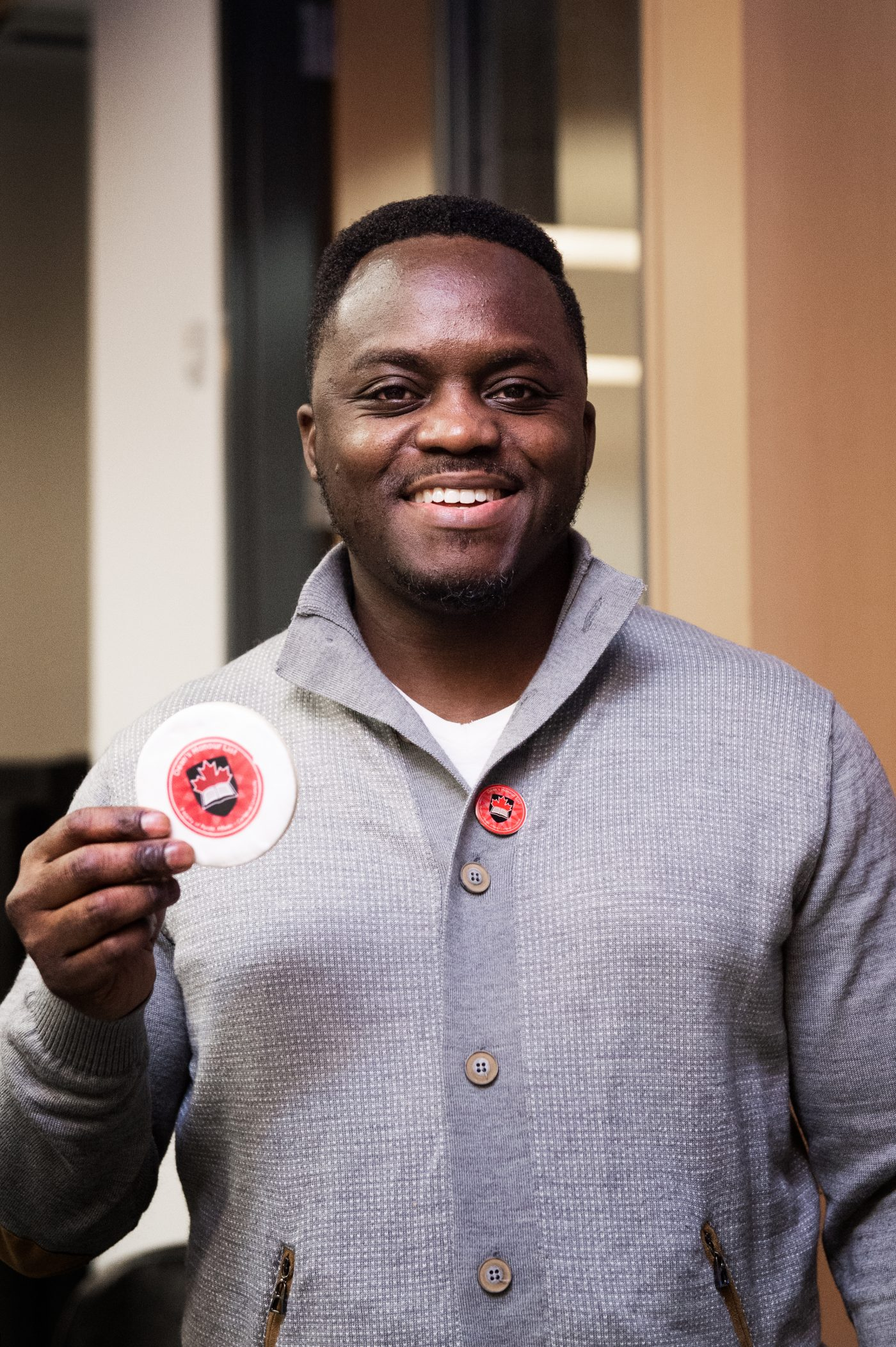 Augustus Morkeh shows off a Dean's Honour List cookie and pin at the reception.