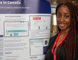 A student poses in front of their poster.