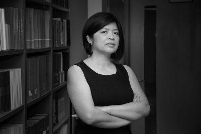 Merlyna Lim poses near bookshelf