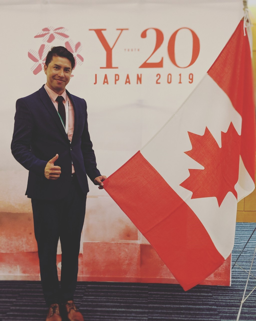 Ali Bahman stands next to a Canadian flag and in front of a sign for the G20 summit in Japan.
