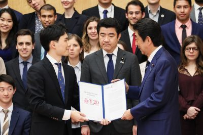 A student presents a certificate to Prime Minister Abe Shenzo as Ali Bahman looks on.