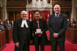 Melanie Adrian receives Senate medal.