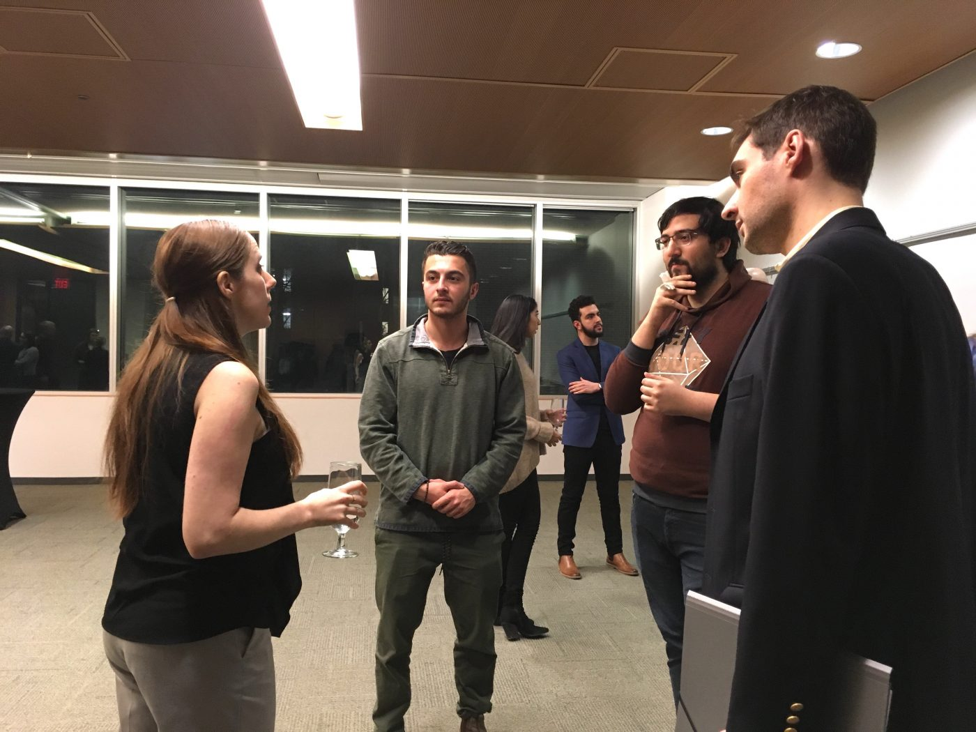 An alumna talks to 3 law students at an event.