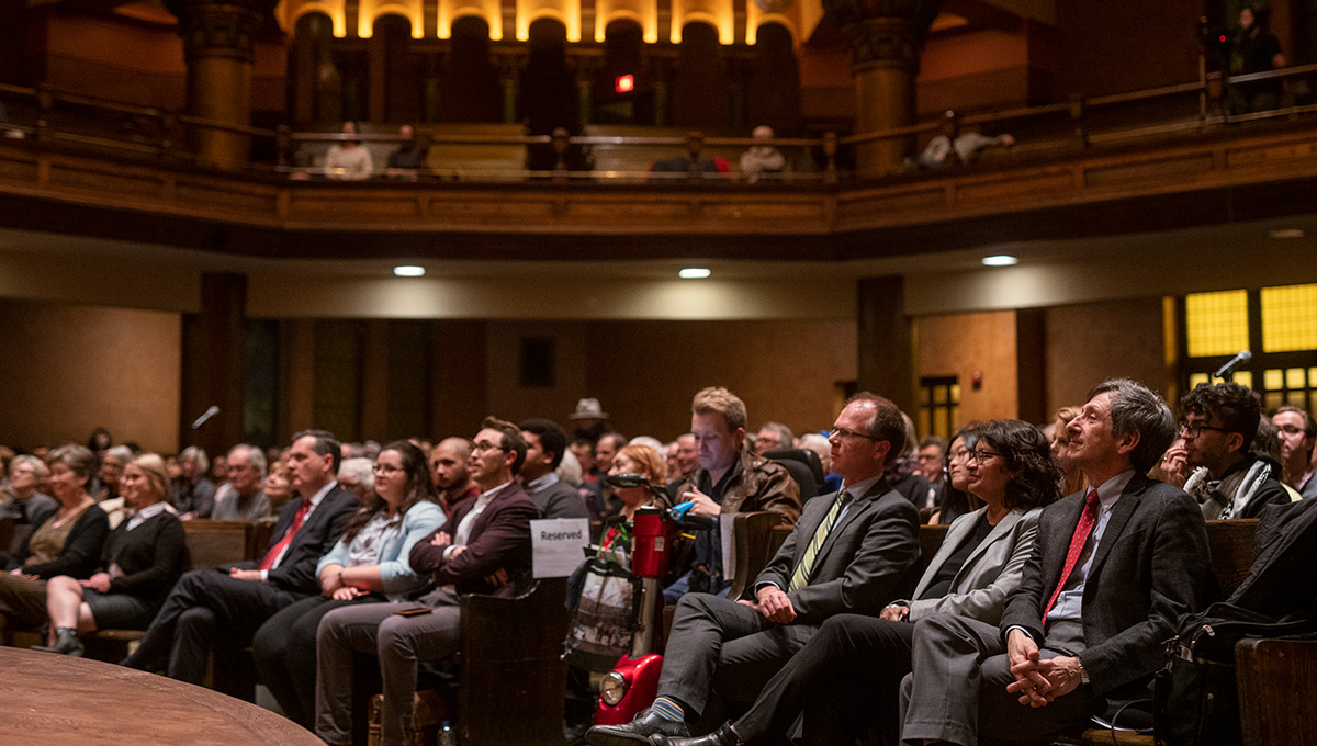 A crowded room including the Dean of the Faculty of Public Affairs watches Notley's lecture