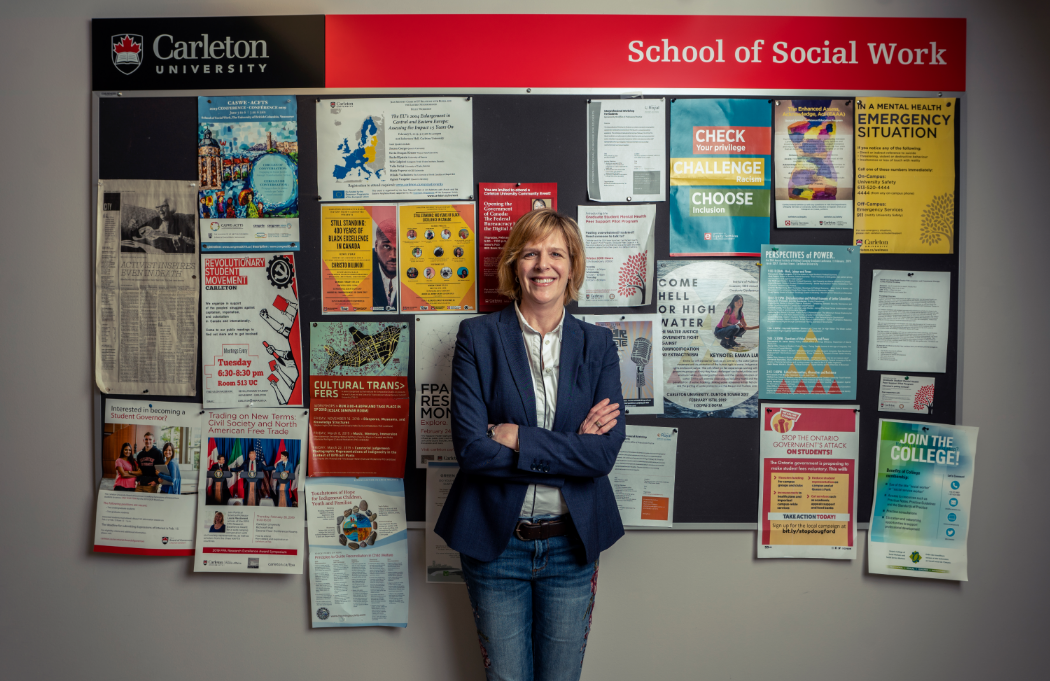 Professor Sarah Todd stands in front a bulletin board in the School of Social Work.