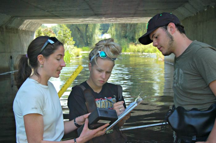 Anna Crawford instructing in the stream with measuring devices