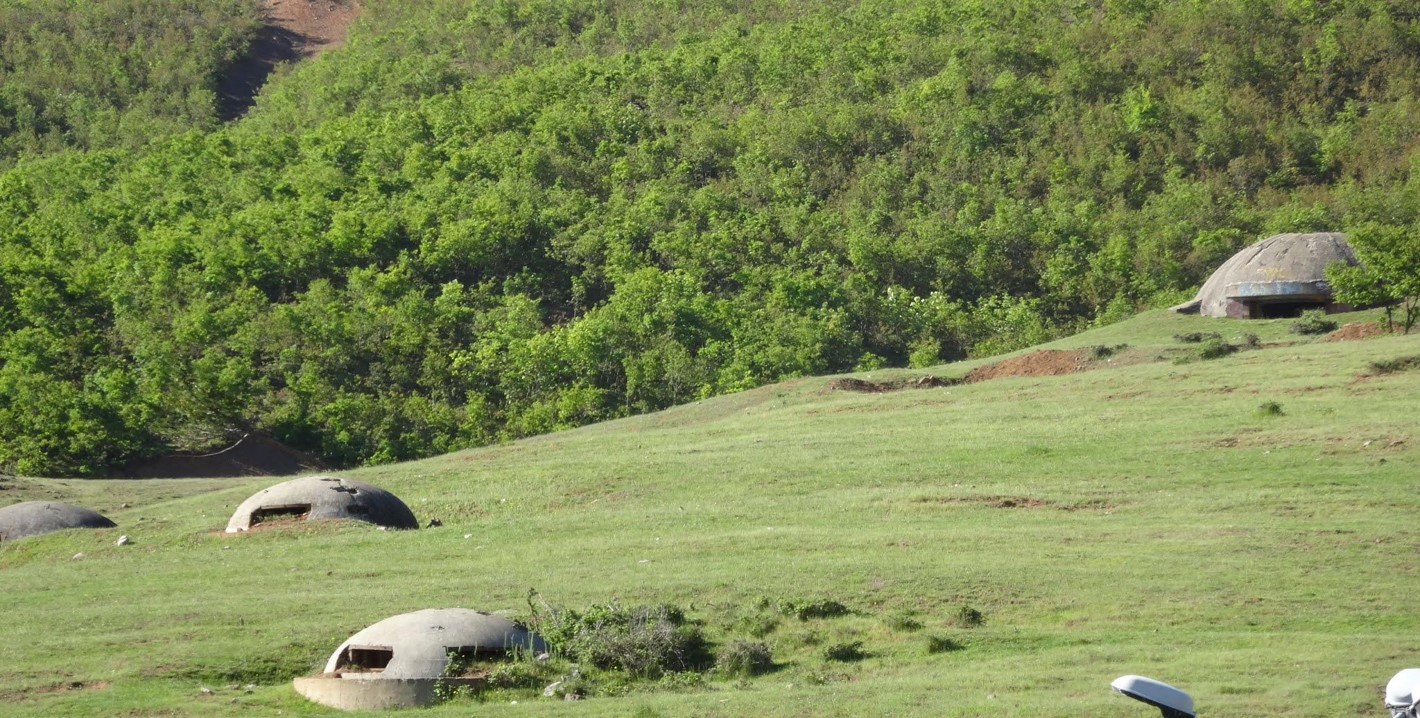 some of Hoxha's bunkers where sheep graze along the road