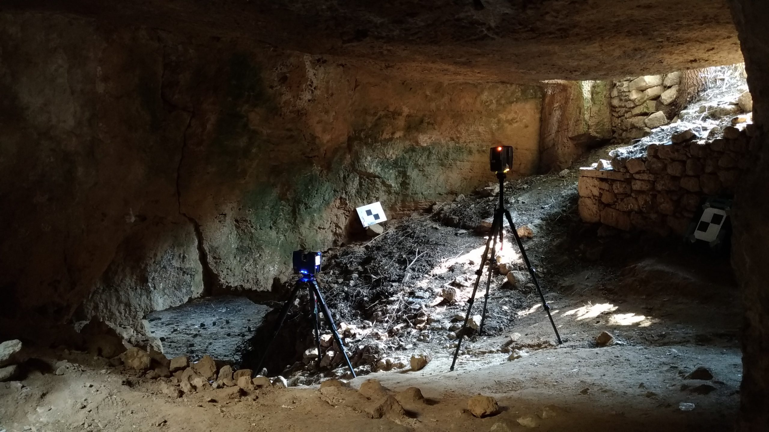 Two laser scanners on tripods standing inside an underground cave with light coming through an opening above.