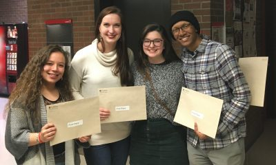 photo of four students standing in a hallway holding envelopes