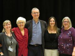 Bruce Elliott standing between four female audience members