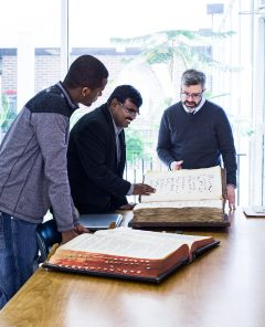 a student with two professors looking over an old book