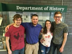 HUgS executive members standing in front of a display case with the words Department of History written above them