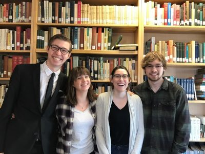 picture of four students standing in front of a wall of books