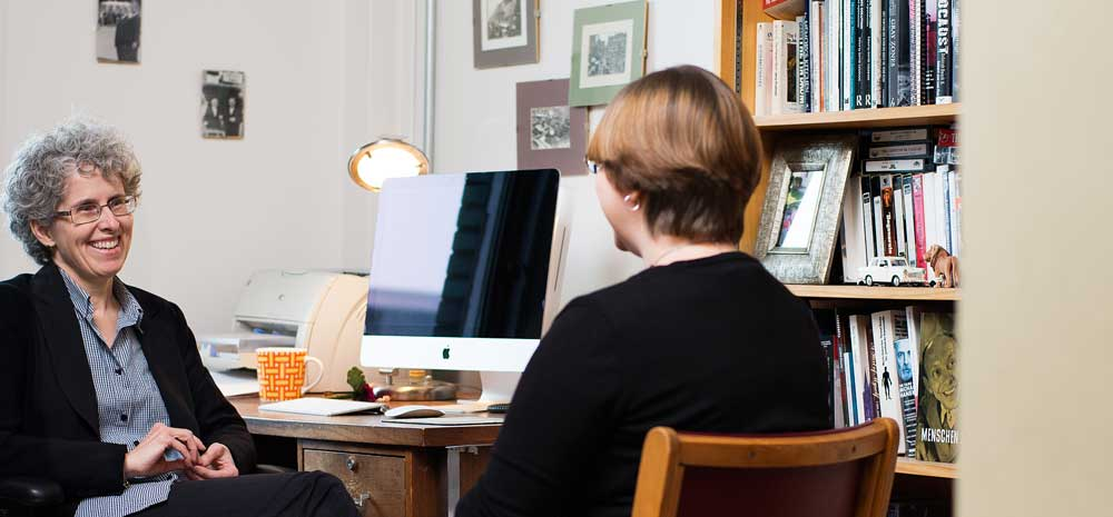 two women talking next to a computer desk