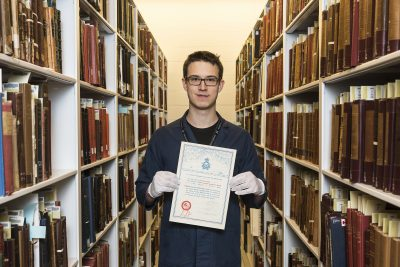 Luka Dursun holding certificate centered amongst books