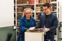 Luka Dursun looking through a book with supervisor Carol Reid