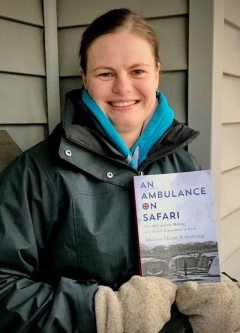 Melissa Armstrong standing outside a house while holding her new book
