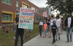 photo of parents and children walking with signs in front of a school