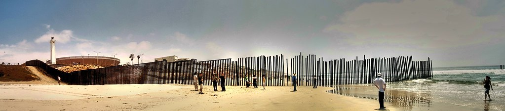 people standing on the beach near a long fence made out of sticks standing straight up
