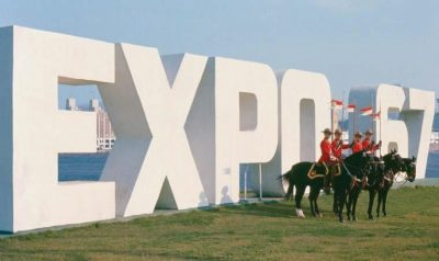 4 RCMP officers mounted on their horses standing on a green field in front of really large letters spelling out Expo 67