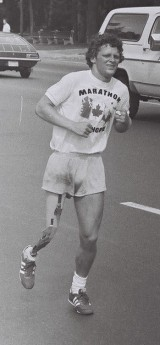 "Terry Fox, a young man with short, curly hair and an artificial right leg runs down a street. He wears shorts and a T-shirt that reads ""Marathon of Hope"""