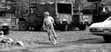 child cycling in front of armoured vehicles