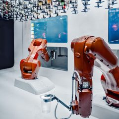 Red robotic arms moving drinking glasses and entering on a computer screen in a white room.
