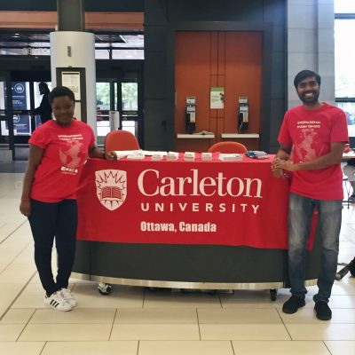Two student staff at Welcome table in their red t-shirts