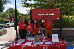Four students sitting in front of a Richcraft Hall sign, standing behind a table covered in Canadian flags and prizes.