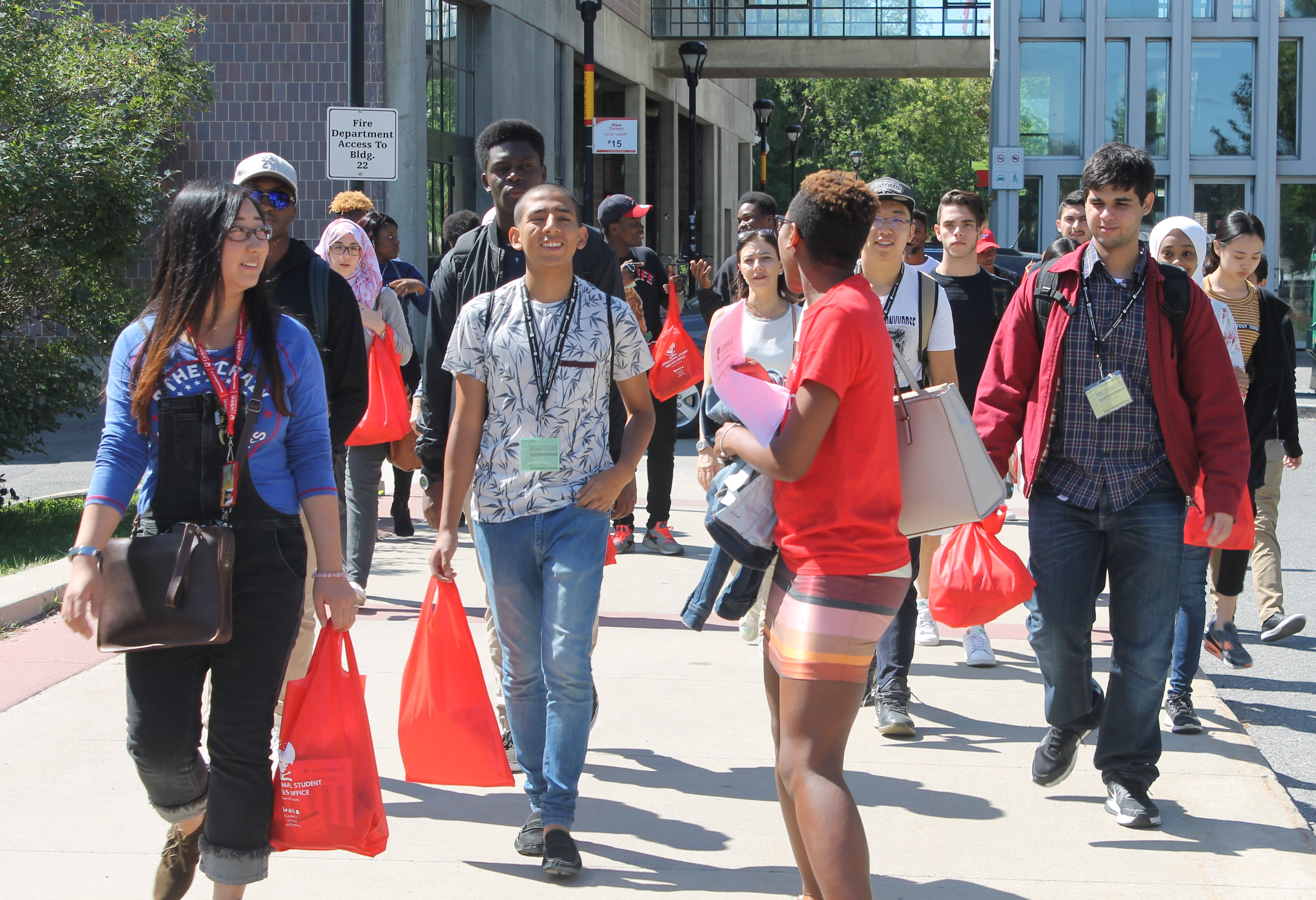 Several Carleton students walking around campus carrying red Orientation bags