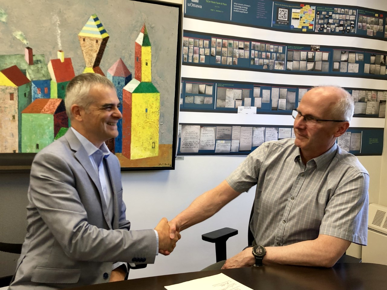 Tim Lott and Martin Bernier shaking hands after signing MOU