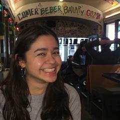 """Valeria in a restaurant.  Sign on the ceiling reads """"comer, beber, bailar, y gozar"""""""