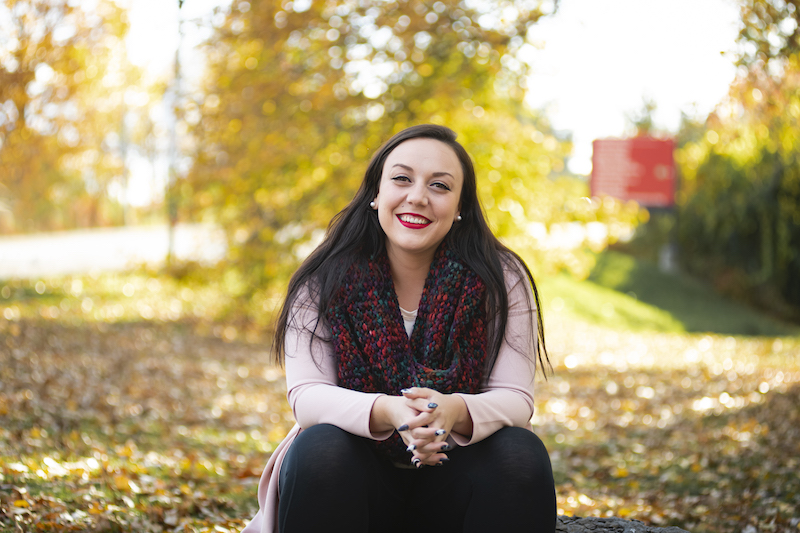 Image of Kaitlan Brazeau sitting outdoors with fall leaves in the background