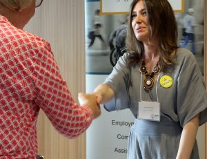 Enable 2019 guest shaking hands with Neil Squire Society representative.
