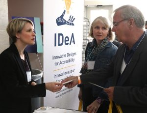 Vendor speaking with attendee at Enable 2019 event at IDEA booth