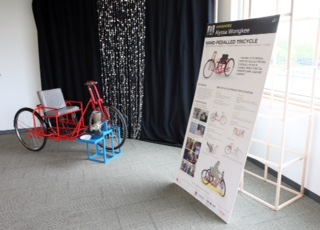 The Harambee project hand-propelled tricycle on display, with accompanying information display board.