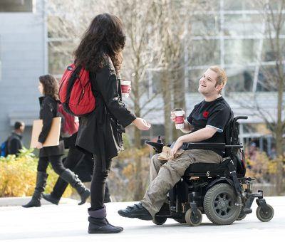 Two students, one using a mobility device, chatting in the courtyard outside the Carleton university centre