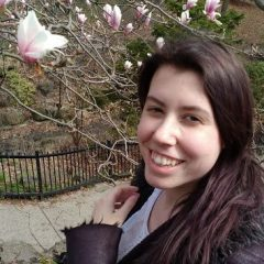 Headshot of Emma Farago outside with white and pink flowers in the background