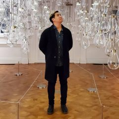 Leon Lu is standing in a room full of hanging lights, looking up towards them.