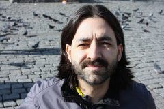 Mahmut Ermedli is outside in the sunlight, squinting at the camera. There are many pigeons in the background behind him.
