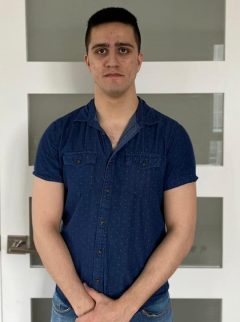 Sami Nassif Lachapelle is wearing a navy polo shirt and standing in front of a white and gray wall, looking at the camera