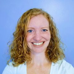 Sarah Moore is smiling at the camera in front of a blue background.