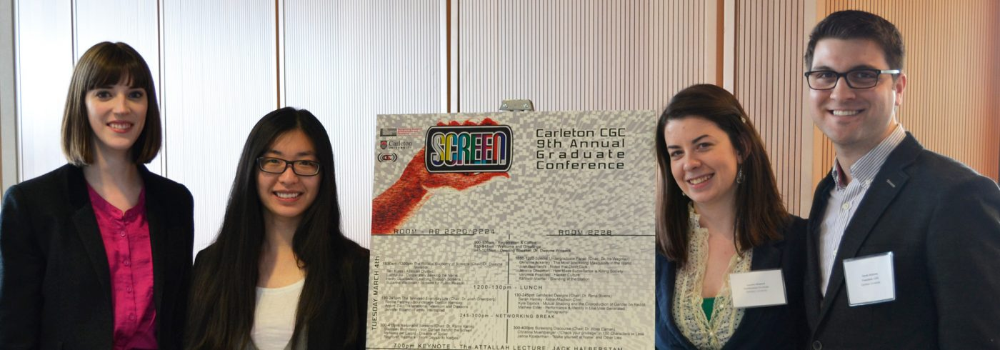 Grad students standing around the schedule for the 9th annual CGC Conference