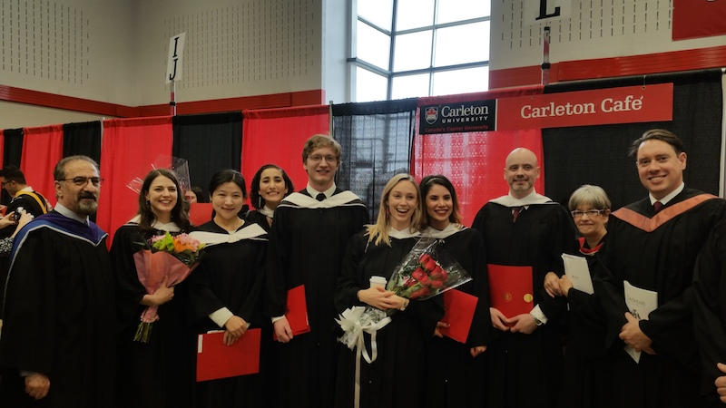 MA grads stand in front of Carleton banners holding diplomas