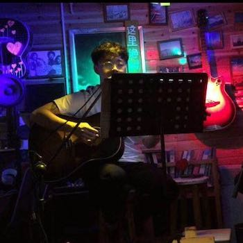 Chunyang sits in a room with a guitar and many different coloured lights