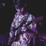 Tomas playing guitar in a Hawaiian shirt