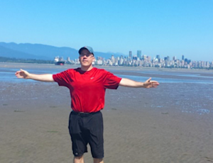 John with his arms outspread with Vancouver behind him
